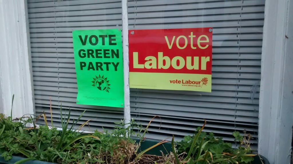 window with Green Party and Labour signs